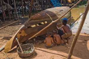 Children learning boat mending from their father, Tonle Sap Lake